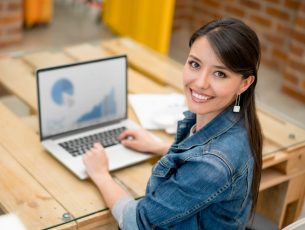 Happy female graphic designer working at the office using her laptop and looking at the camera smiling